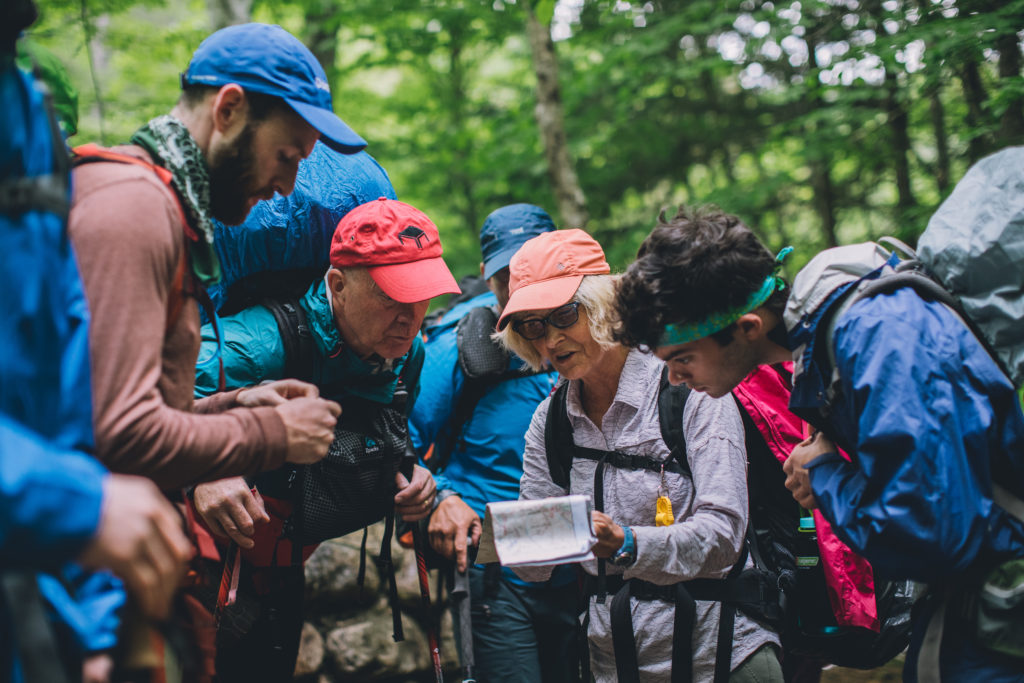 Several hikers consult a trail map