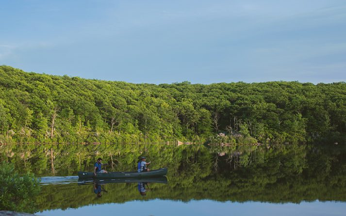 Canoeists on Breakneck Pond at the Stephen & Betsy Corman AMC Harriman Outdoor Center.
